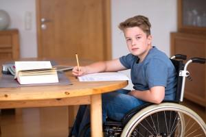 boy in wheelchair doing homework