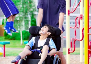 Disabled boy in wheelchair enjoying watching friends play at park